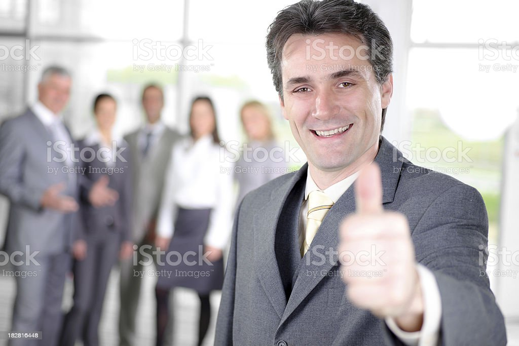 Young friendly business man pointing okay, behind her colleagues royalty-free stock photo