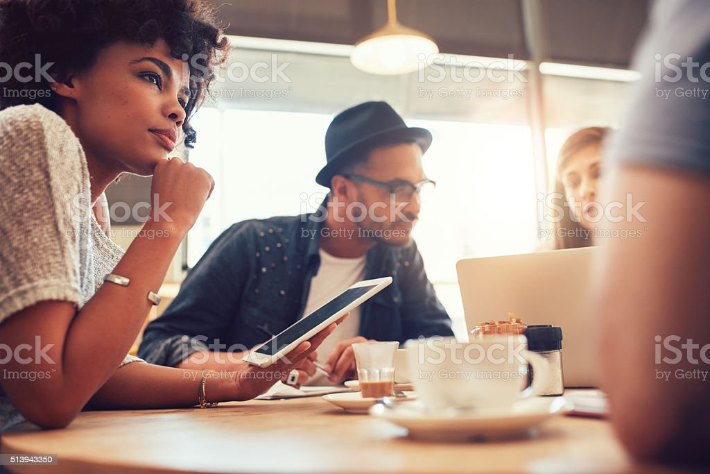 Young friends at a coffee shop with laptop stock photo