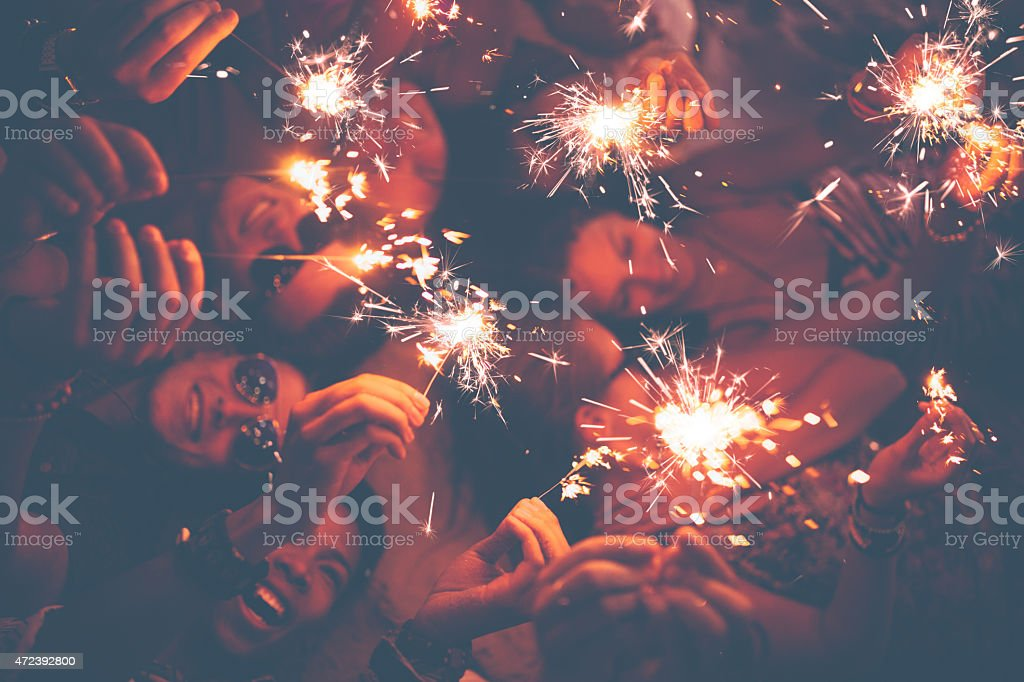 Young friends celebrating with sparklers at a beachparty stock photo