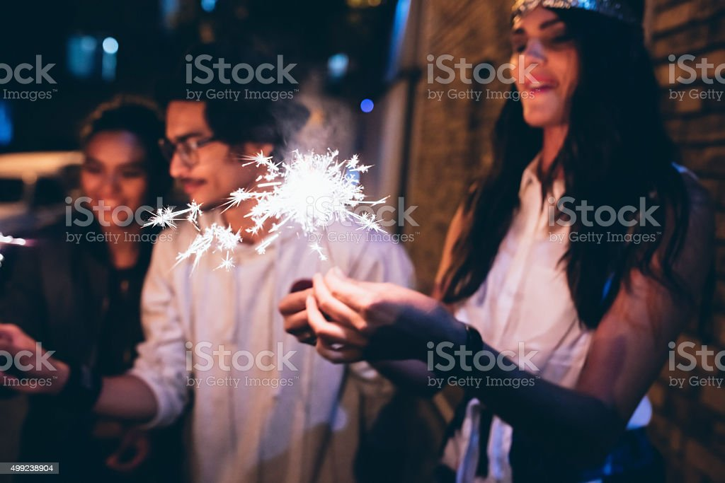 Young friends celebrating with sparklers stock photo