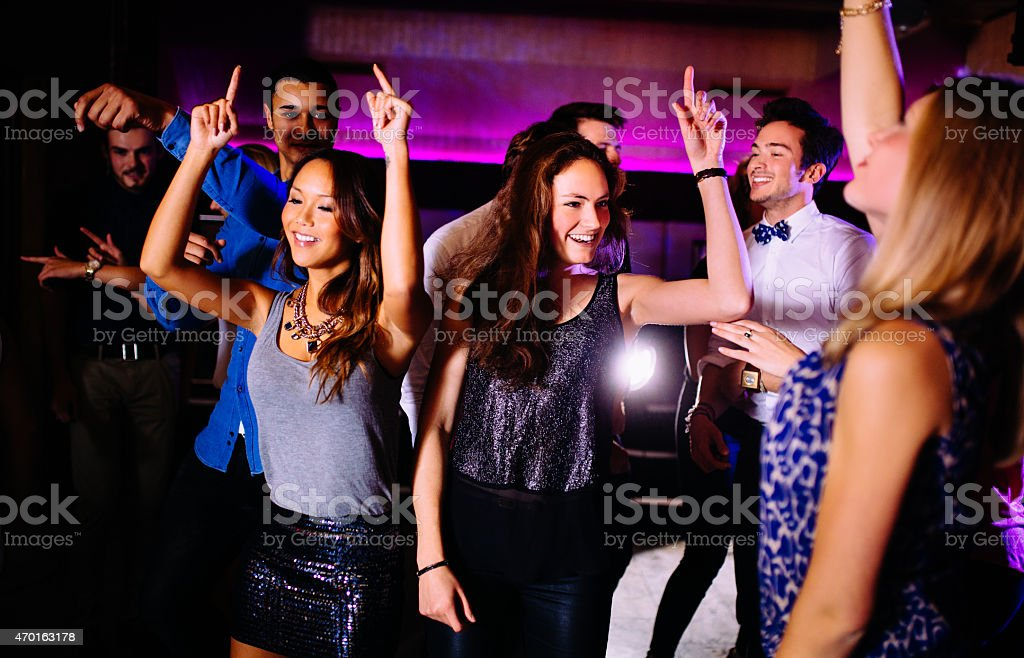 Young friends dancing in a group in a night club stock photo