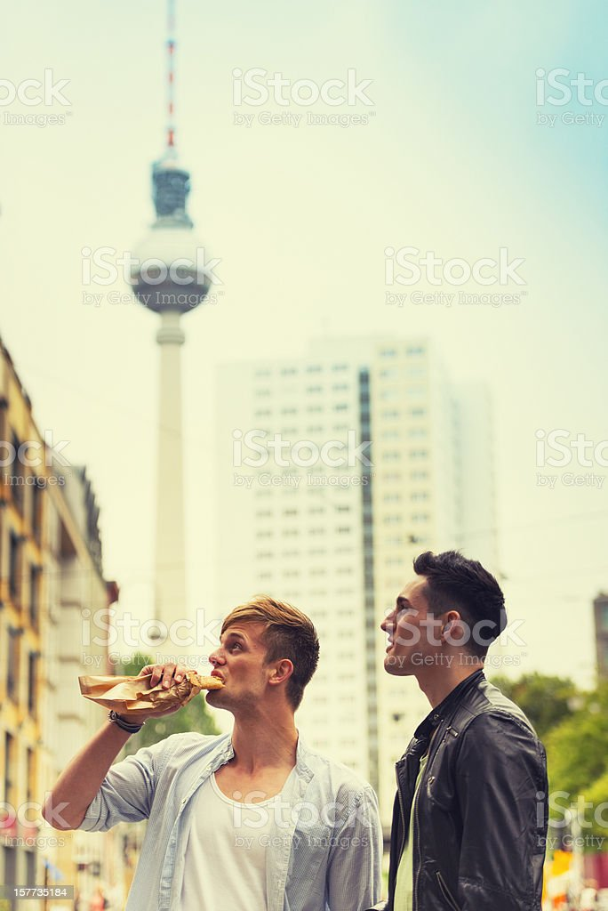 Young friends eating a baguette under the tv tower. Berlin royalty-free stock photo
