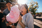 Young friends eating cotton candy outdoors