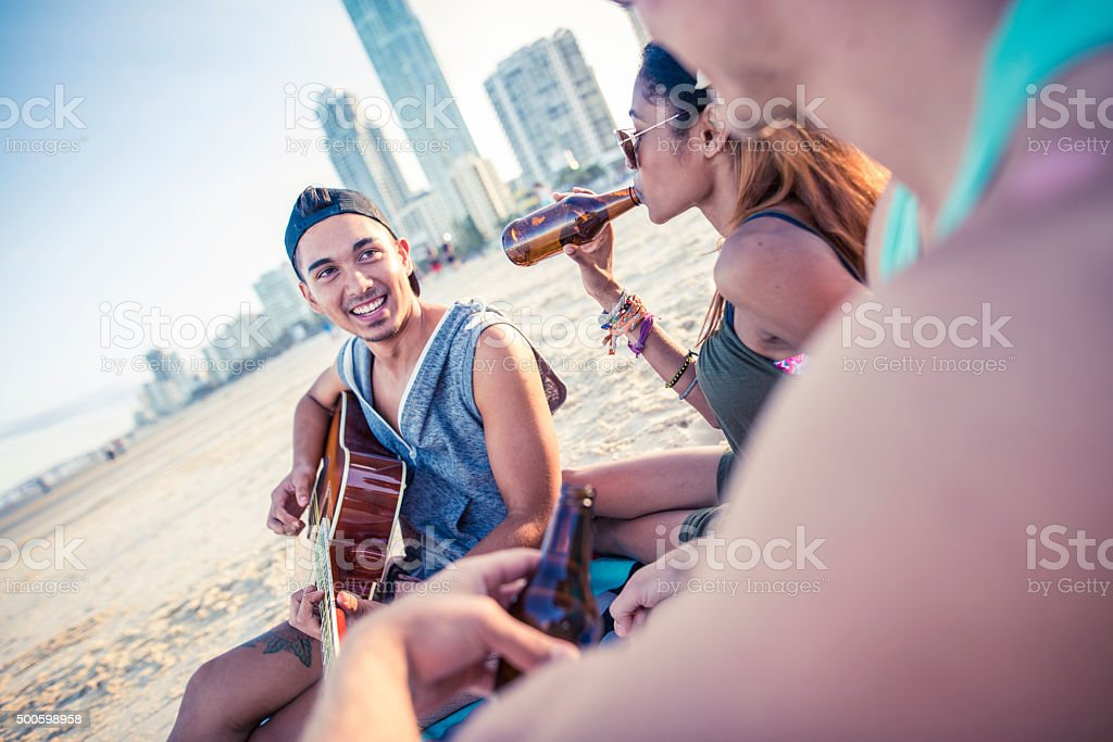 Young friends enjoying a beach party stock photo