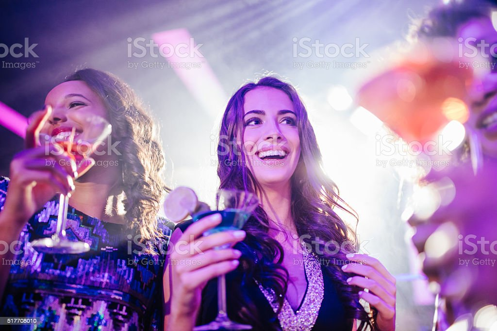 Young friends enjoying party with colorful drinks at the club stock photo