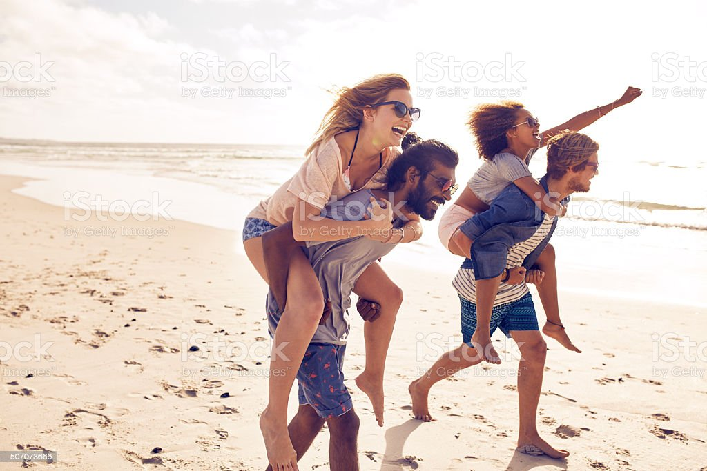 Young friends enjoying summertime on the beach stock photo