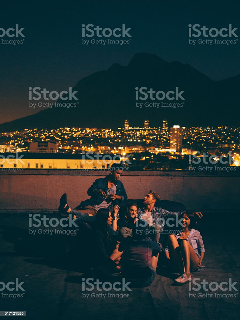 Young friends hanging out on the rooftop for a party stock photo