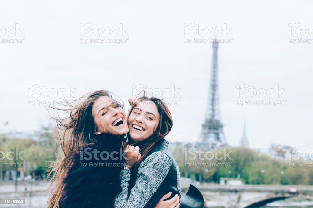 Young friends having fun in front of Eiffel tower stock photo