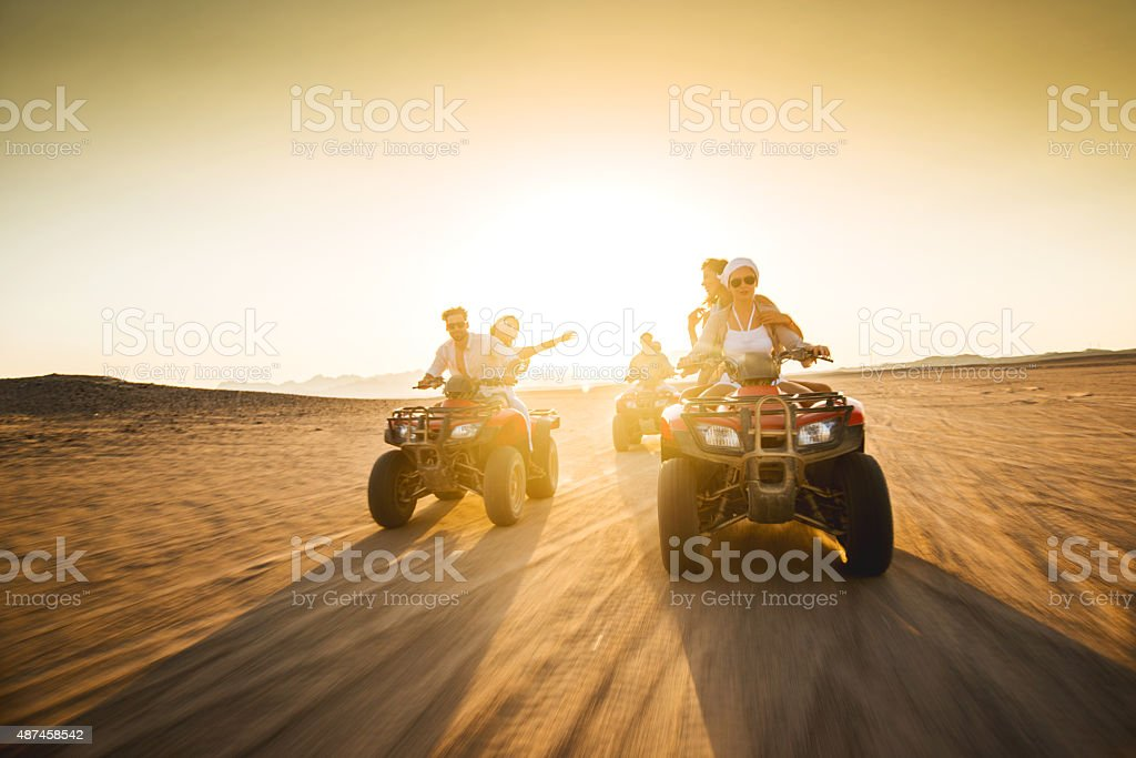 Young friends having fun on quad bikes at sunset. stock photo