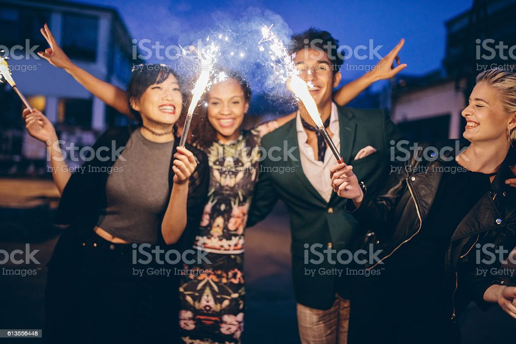 Young friends having night party with sparklers stock photo