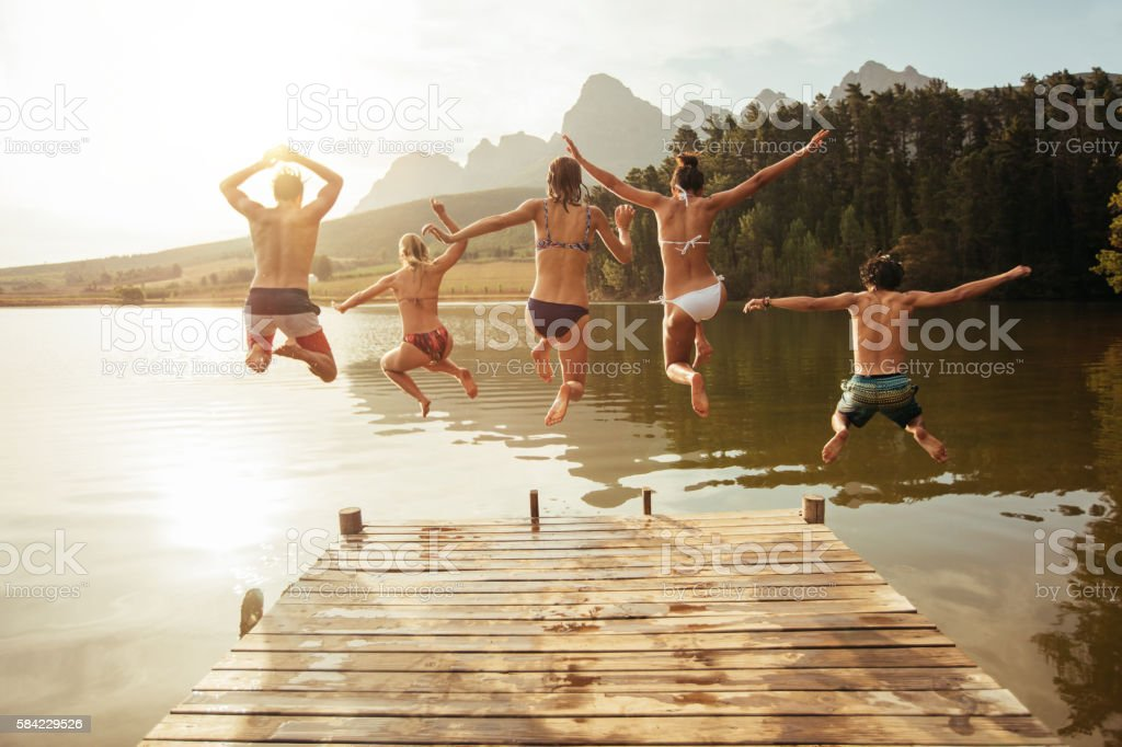 Young friends jumping into lake from a jetty stock photo