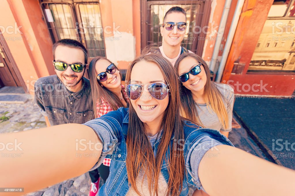 Young friends laughing and taking selfie stock photo