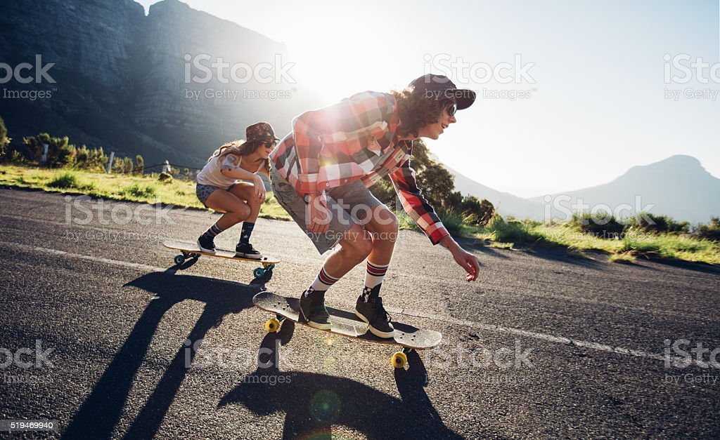 Young friends longboarding down the road stock photo