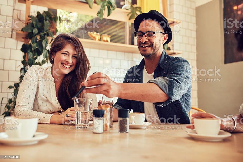 Young friends looking at smart phone while sitting in cafe stock photo