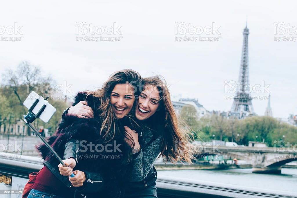 Young friends making selfie with monopod on a bridge stock photo