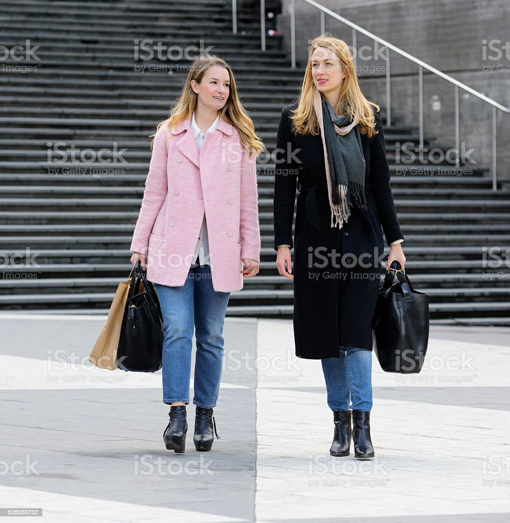 Young friends on street walking on city square stock photo