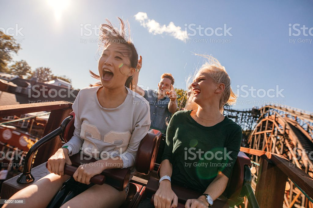 Young friends on thrilling roller coaster ride stock photo