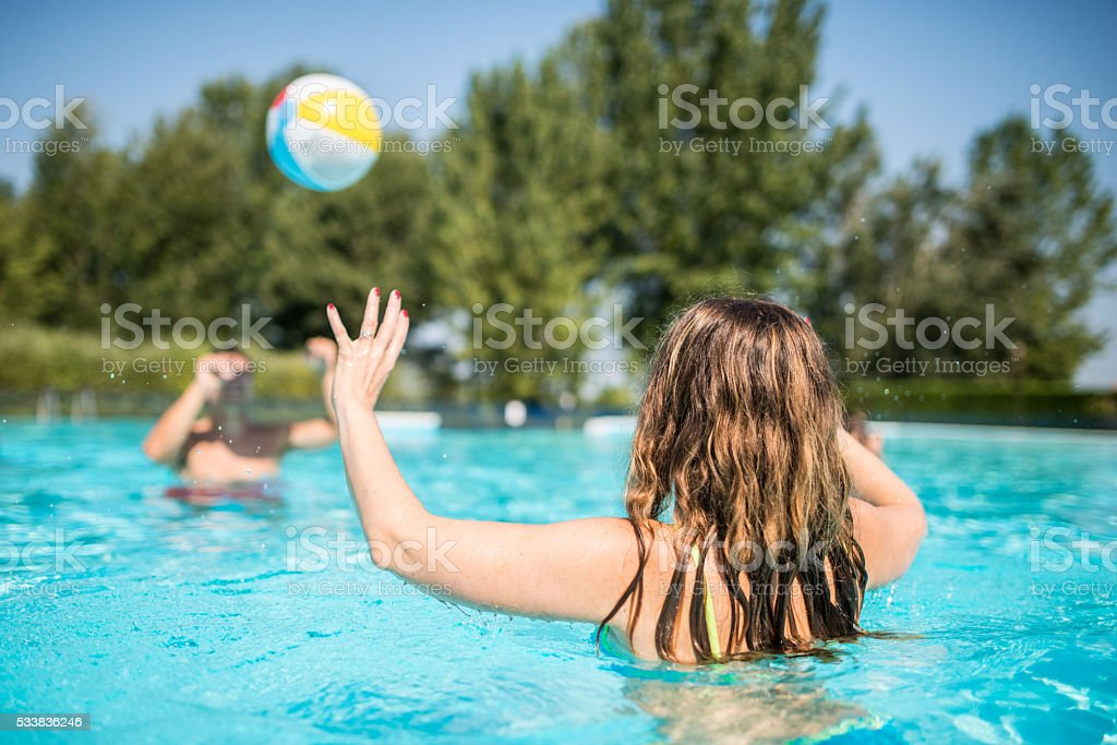 Young friends play in swimming pool stock photo