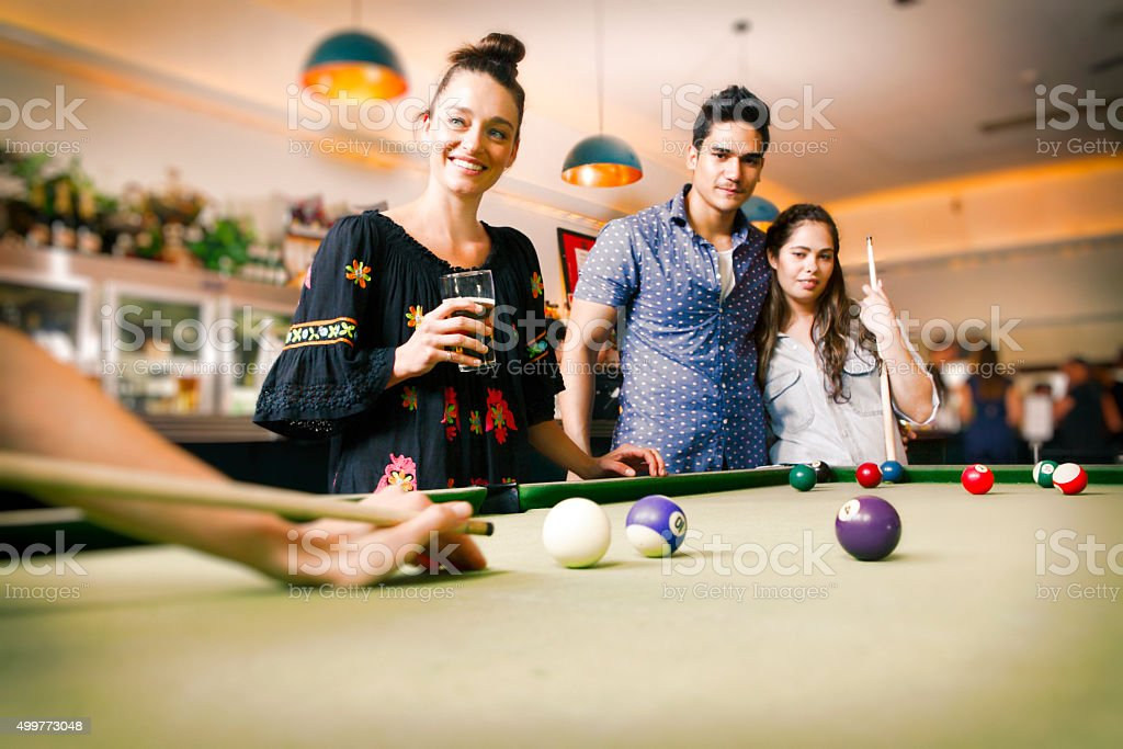 Young friends playing billiard in the pub stock photo