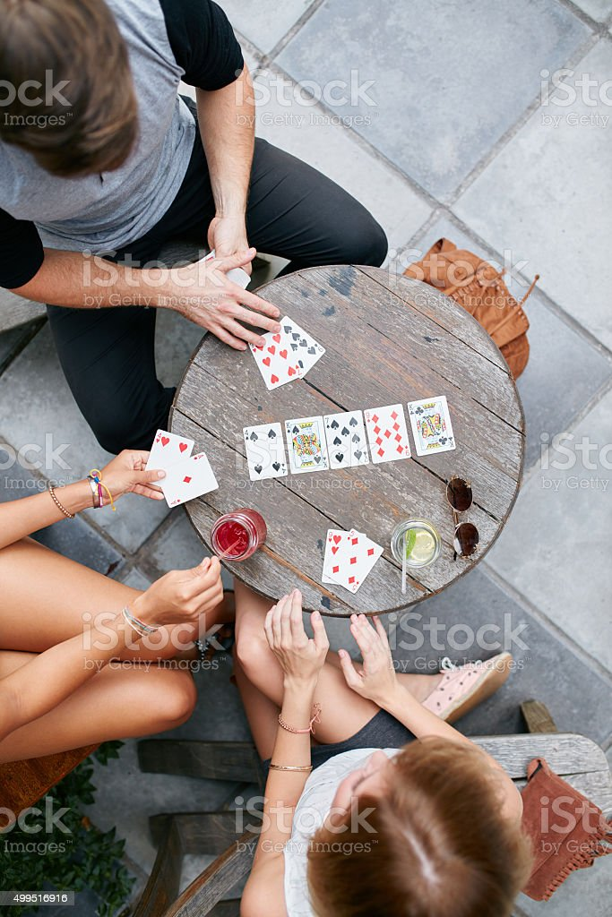 Young friends playing poker card game at cafe stock photo