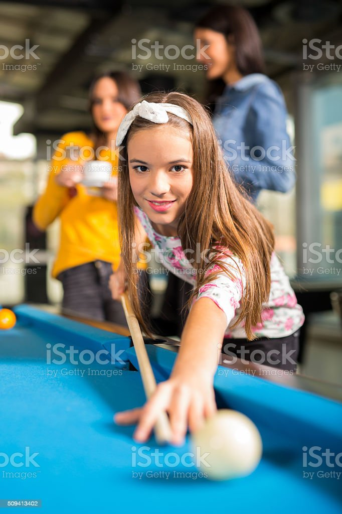 Young friends playing pool or billiard stock photo