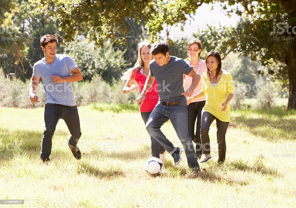 Young Friends Playing Soccer In Countryside stock photo