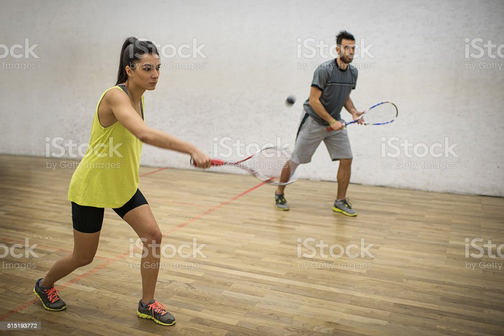 Young friends playing squash together on a court. stock photo