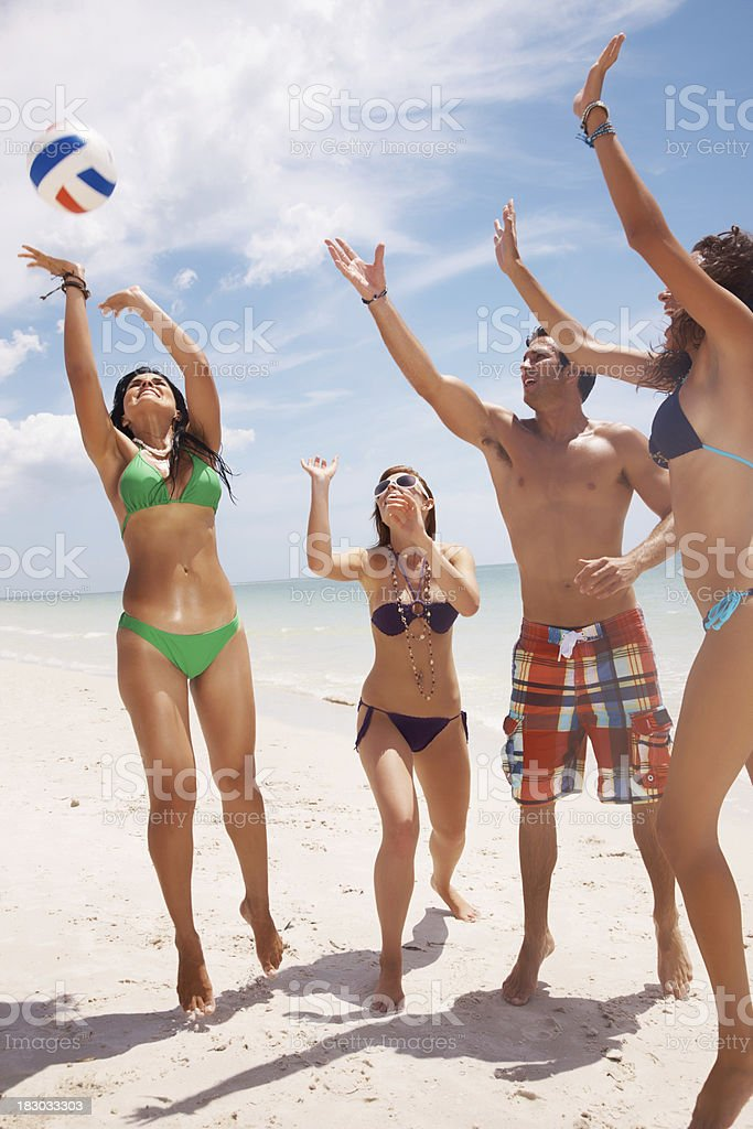 Young friends playing volleyball on beach royalty-free stock photo