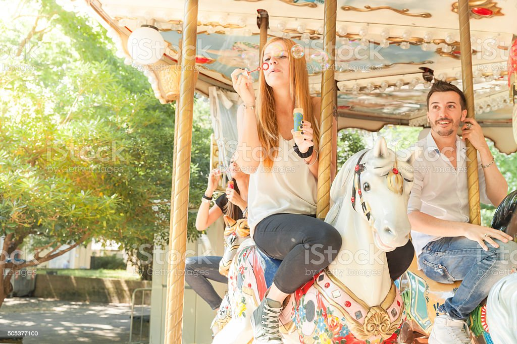 Young friends playing with soap sud riding carousel horses stock photo