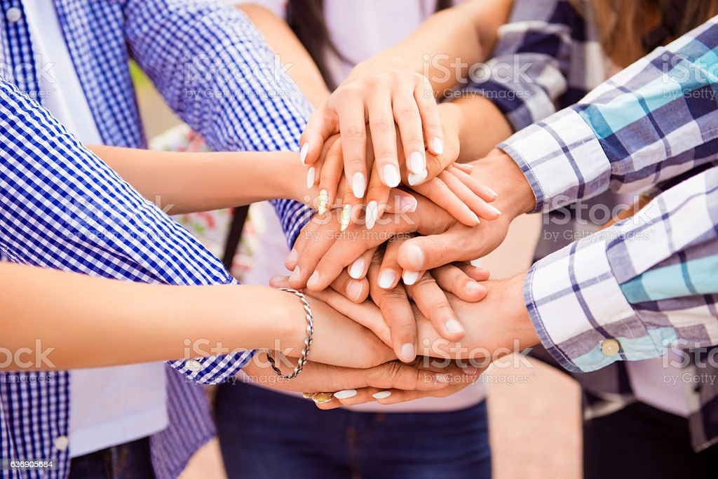 young friends putting their hands on top of each other. stock photo