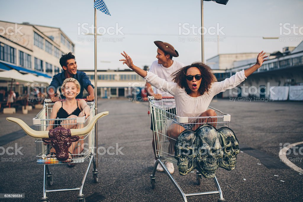 Young friends racing with shopping carts stock photo