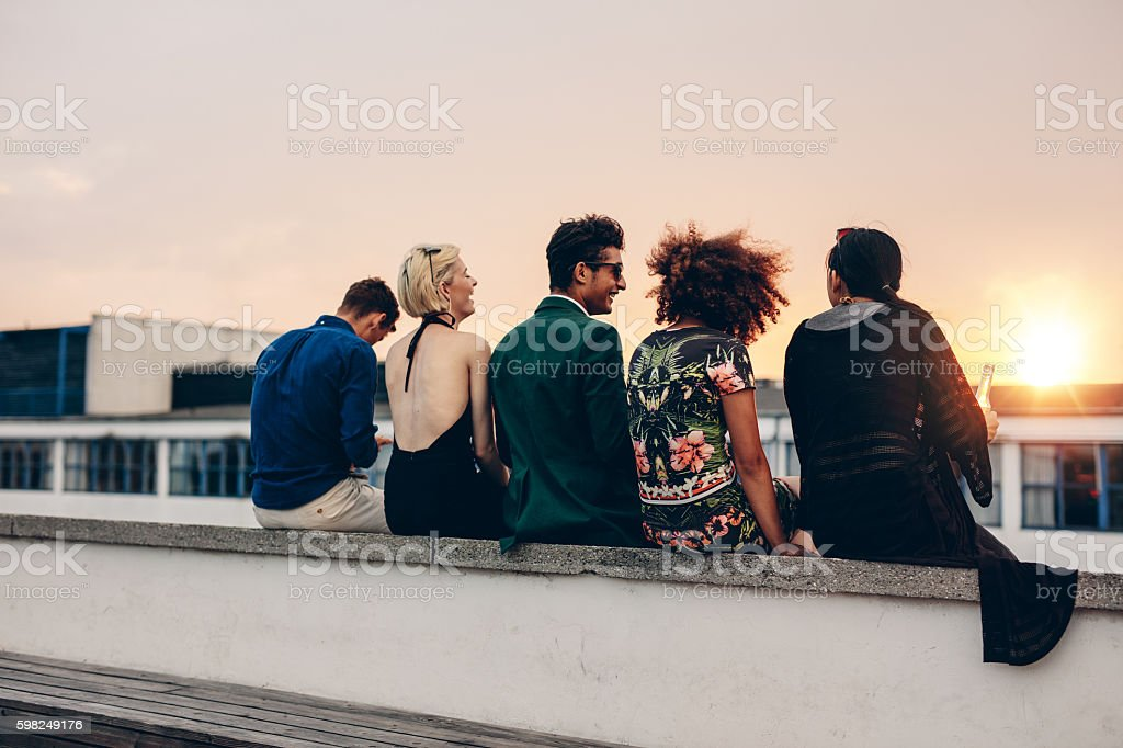 Young friends relaxing on terrace during sunset stock photo