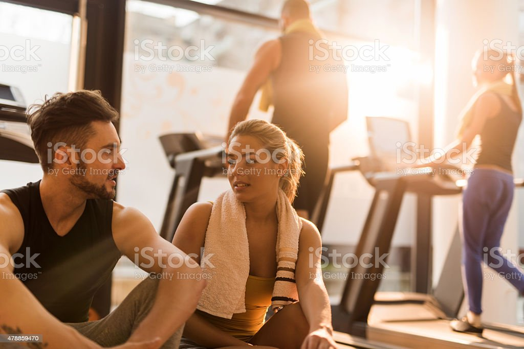Young friends resting from exercising in gym and communicating. stock photo