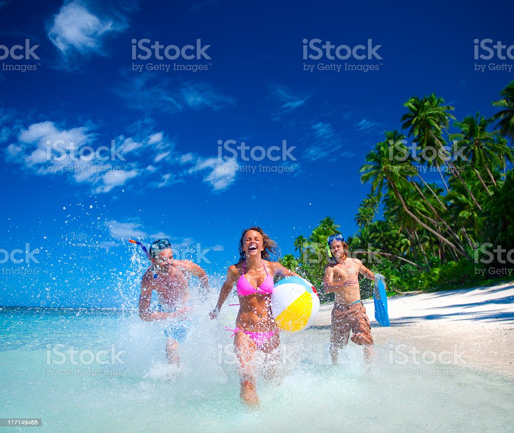 Young friends running in the sea at the beach royalty-free stock photo