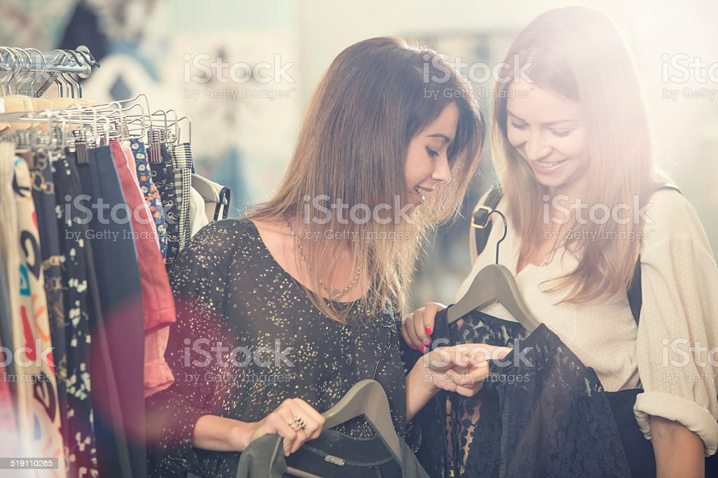 Young friends searching clothes in secondhand clothing shop stock photo