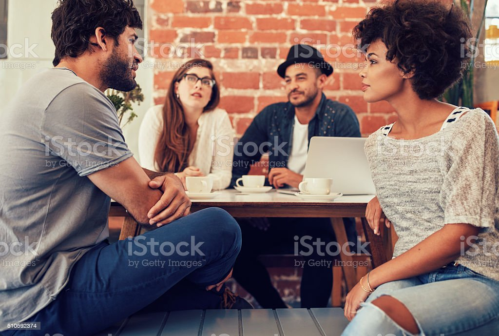 Young friends sitting and talking at a coffee shop stock photo