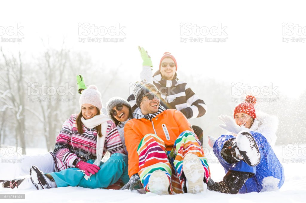 Young friends sitting in winter snow and having fun stock photo