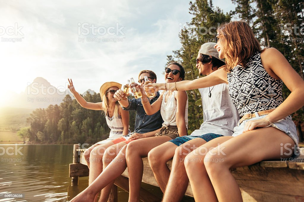 Young friends sitting on a pier toasting beers stock photo