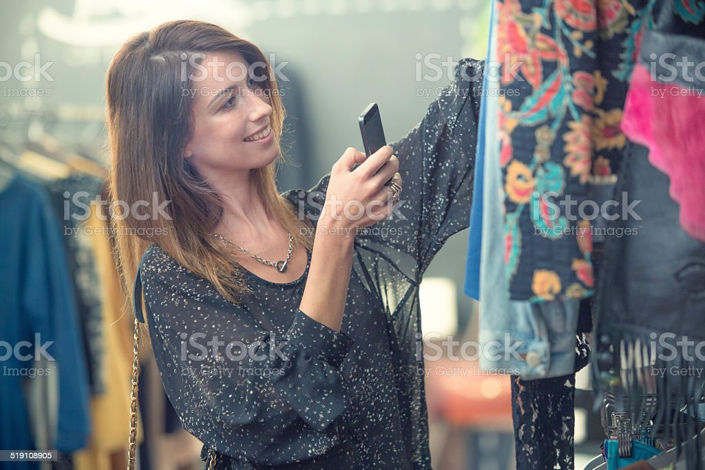 Young friends take clothes photos in secondhand clothing shop stock photo