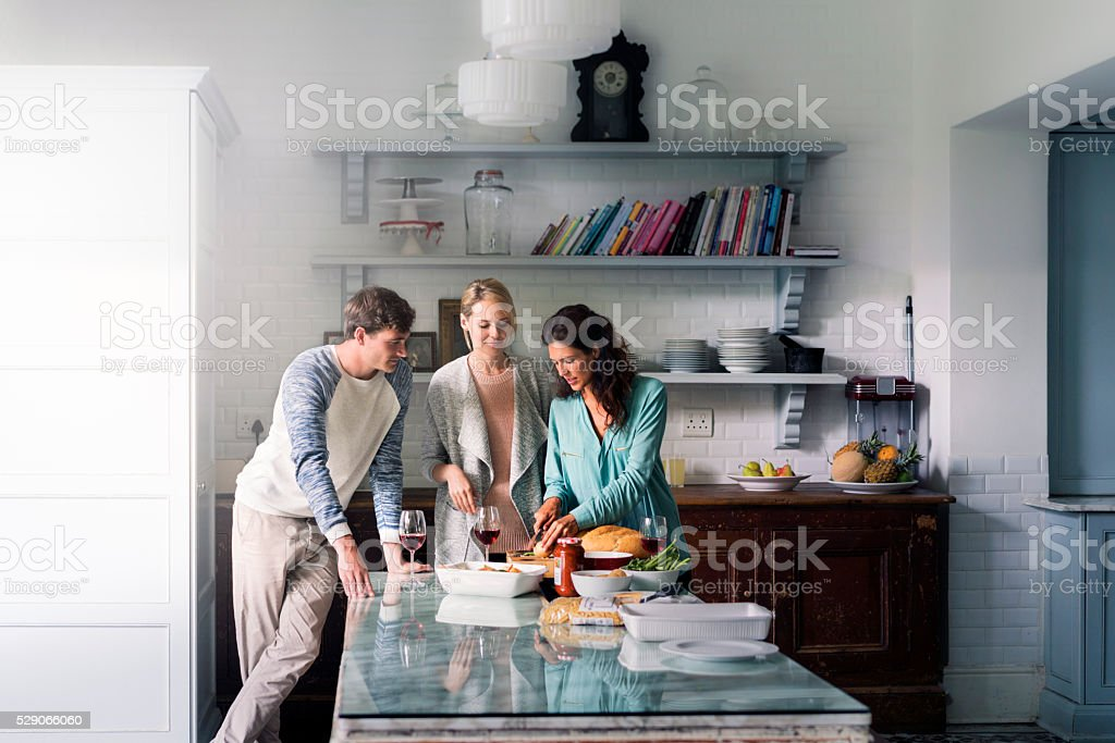 Young friends talking and cooking food at home stock photo