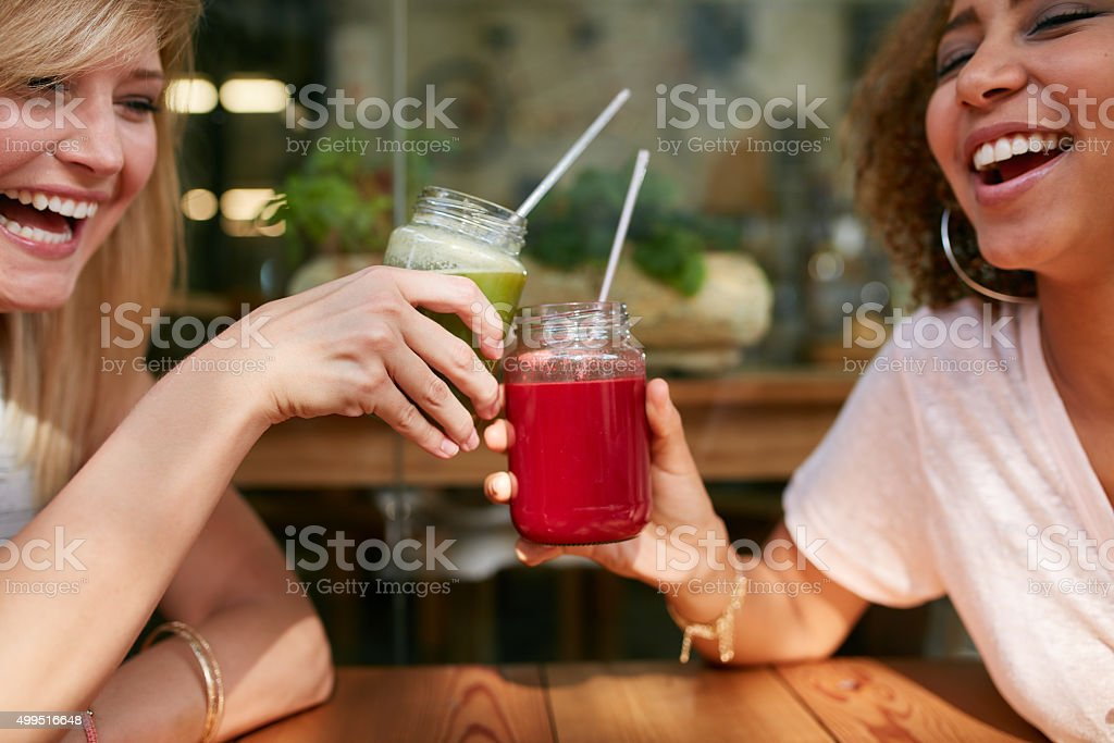 Young friends toasting drinks at sidewalk cafe stock photo
