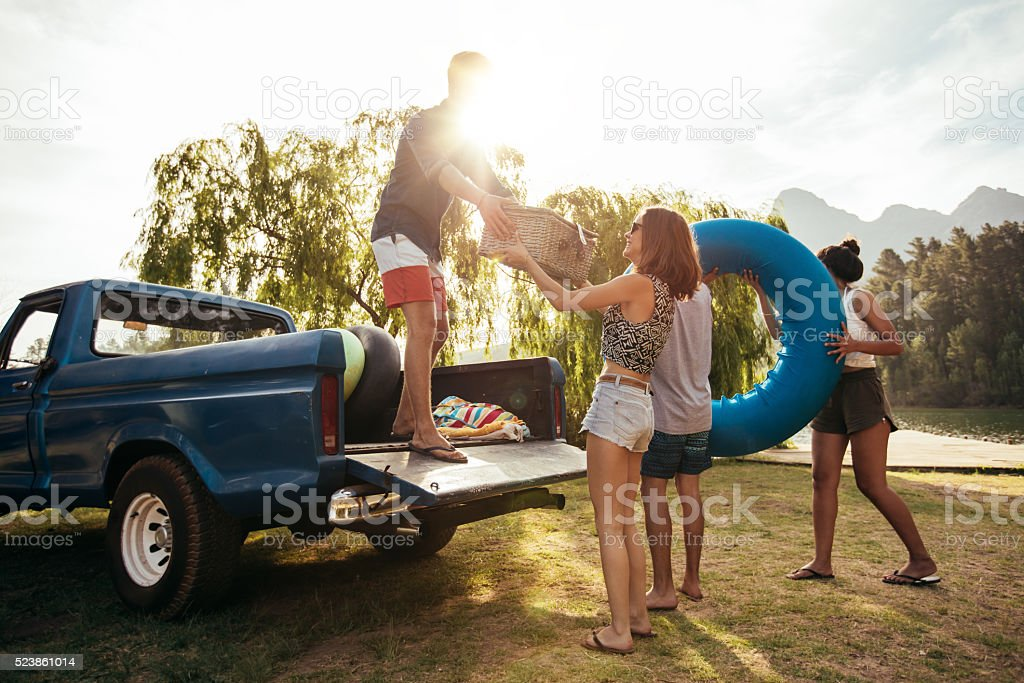 Young friends unloading pickup truck on camping trip stock photo