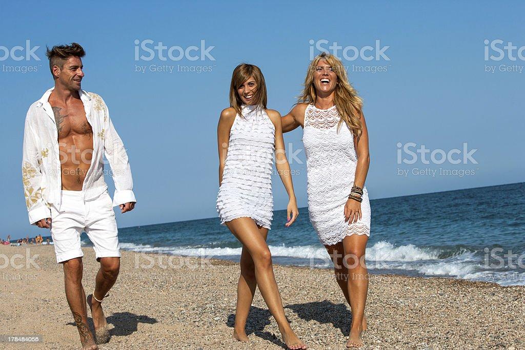 Jeunes amis marchant le long de plage ensoleillée. photo libre de droits