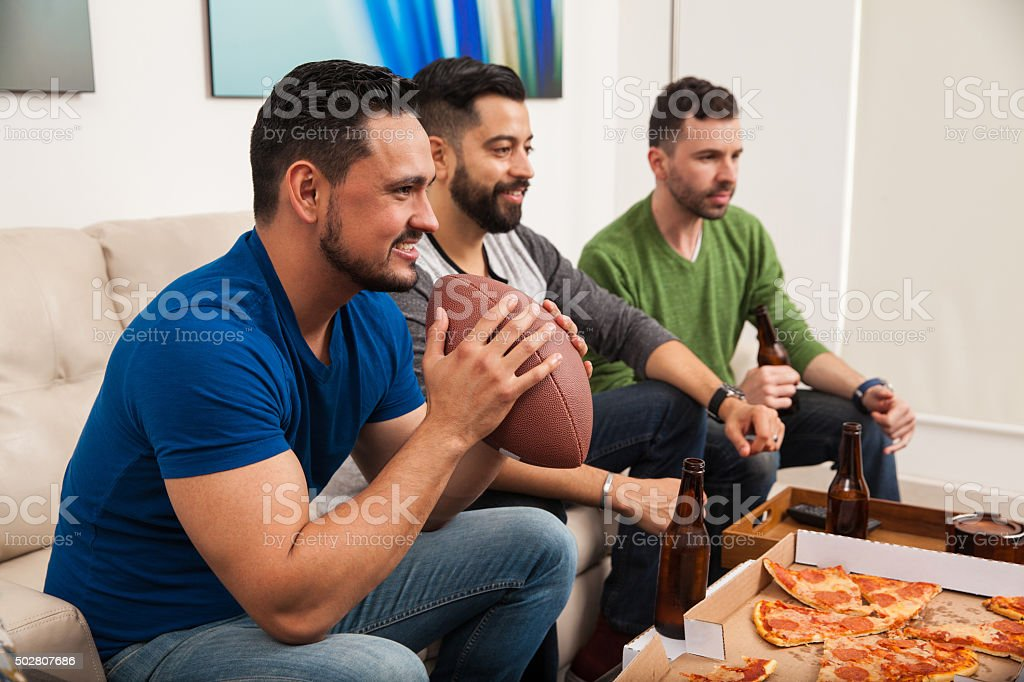 Young friends watching a football game stock photo