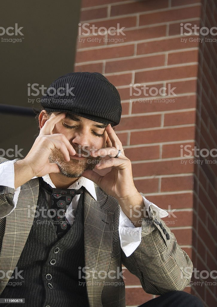 Young frustrated businessman sitting in front of a office building stock photo