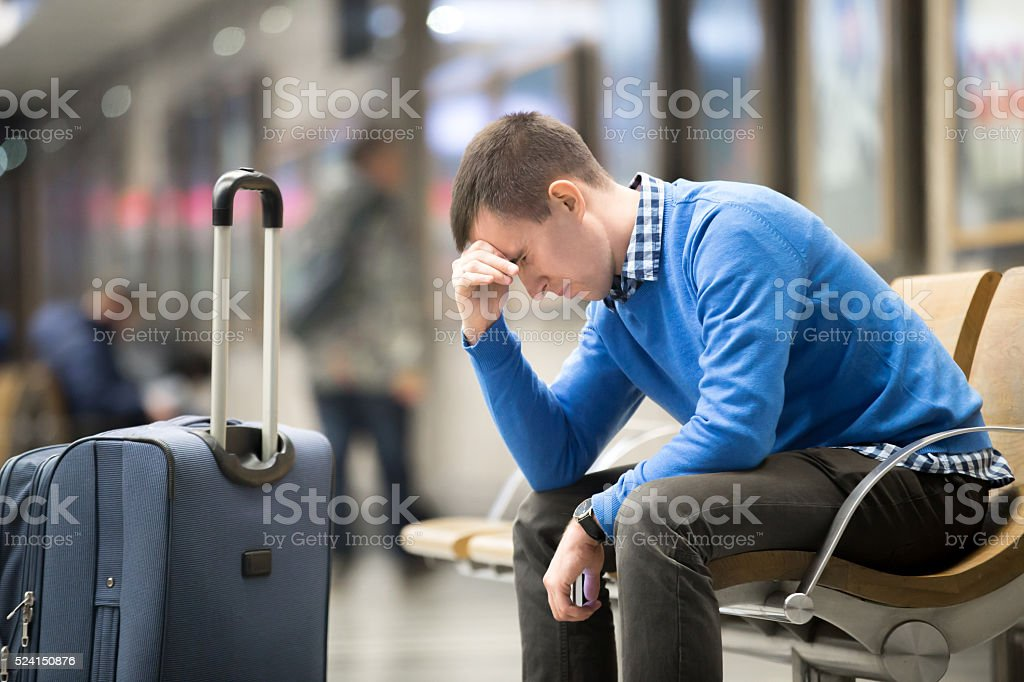 Young frustrated man at airport stock photo