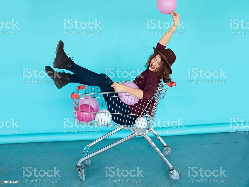 Young funky woman sitting in shopping cart over blue wall stock photo