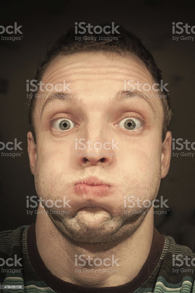 Young funny Caucasian man inflates cheeks. Closeup portrait stock photo