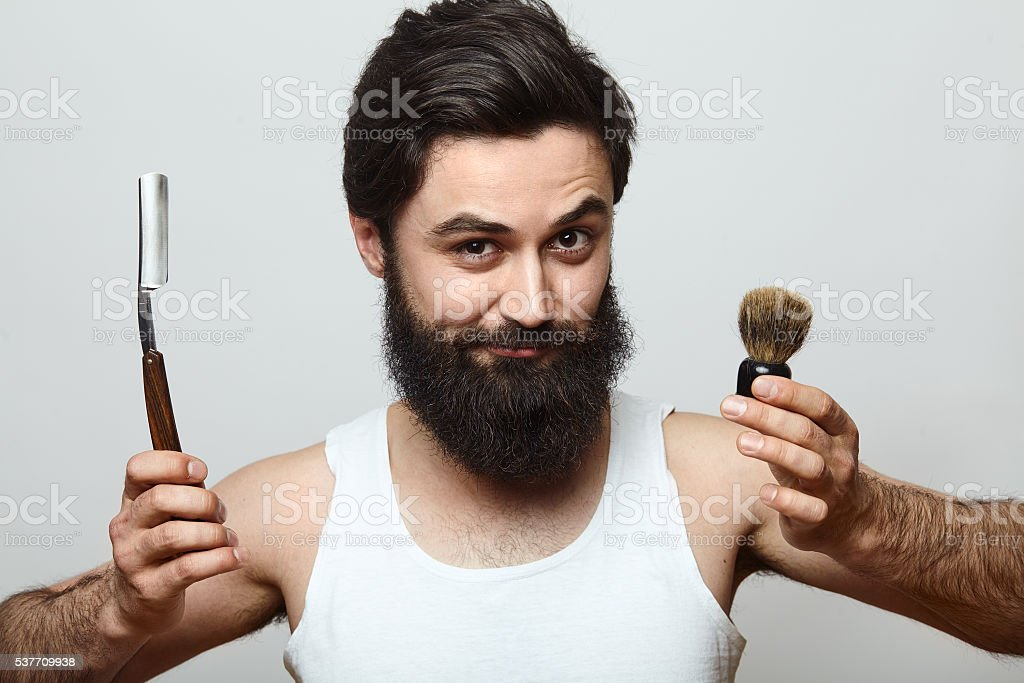 young funny man guy with beard showing razor blade stock photo