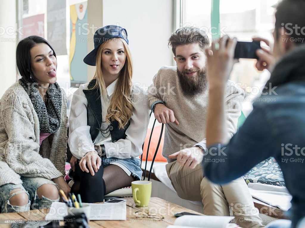 Young funny people being photographed by their friend at cafe. stock photo